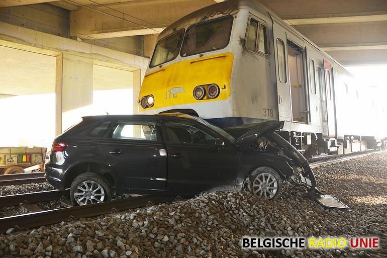 Auto onder trein, bestuurster ongedeerd