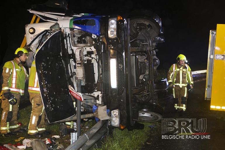 Vrachtwagen maait verlichtingspaal omver en kantelt, bestuurder gekneld