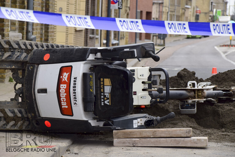 Arbeider gekneld onder gekantelde Bobcat graafmachine